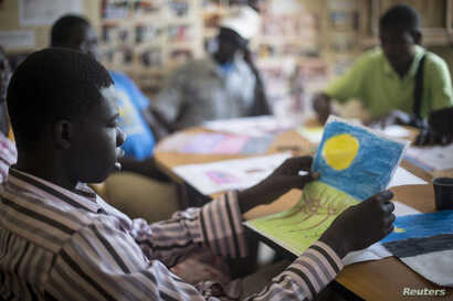 FILE - Patients undergoing a rehabilitation program draw during a therapy session at the Sopi Jikko centre in Dakar, June 6, 2014. Sopi Jikko is a rehabilitation center for people with mental health and drug addiction problems.