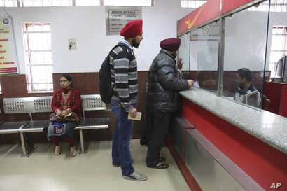 Indians stand to deposit discontinued currency notes at a post office on the outskirts of Jammu, India, Dec. 29, 2016.