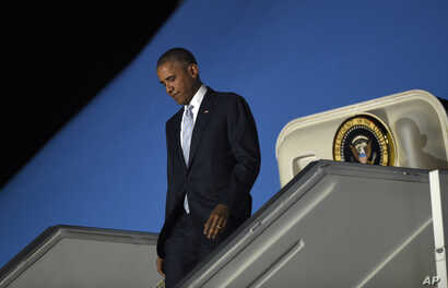 President Barack Obama walks down the steps of Air Force One after arriving at Chopin Airport in Warsaw, Poland, Friday, July 8, 2016.