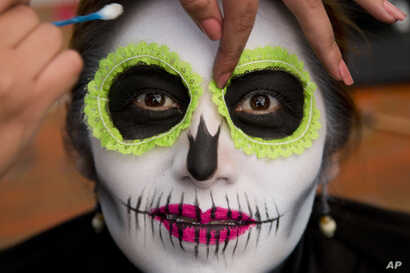 A woman has her makeup applied as she waits for the start of a Day of the Dead parade to begin along Mexico City's main Reforma Avenue, Oct. 28, 2017.