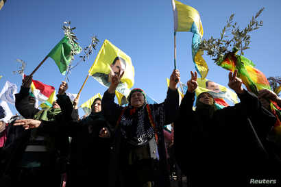 People gesture during a protest against the Turkish attacks on Afrin in Qamishli, Syria, Jan. 30, 2018.