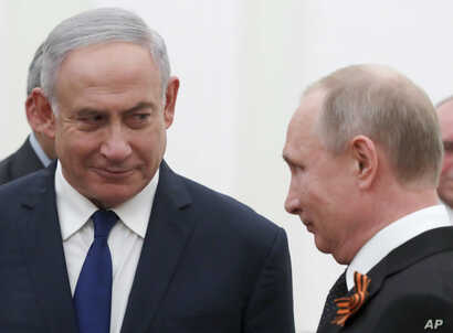 Russian President Vladimir Putin, right, and Israeli Prime Minister Benjamin Netanyahu talk to each other during their meeting in the Kremlin in Moscow, Russia, May 9, 2018.
