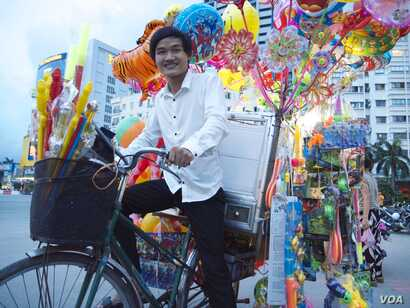 Pham Minh Dap, 24, sells balloons and children's toys outside a park in Hanoi. He uses the money to fund a free language school for poor students, Hanoi, Vietnam, Aug. 7, 2014. (Marianne Brown/VOA)