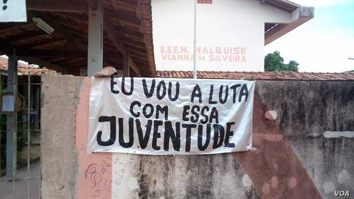 "A sign reads ""I shall fight together with this generation,"" implying that someone from the older generation will support today's youth in its quest to achieve education reform, at an occupied high school in Para State, northern Brazil. (Photo – c..."