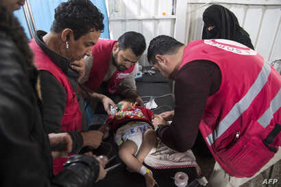 Syrian medics treat a baby at a makeshift clinic at the internally displaced persons camp of al-Hol in al-Hasakah governorate in northeastern Syria, Feb. 6, 2019.