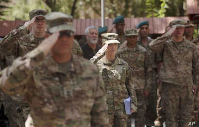 FILE - U.S. soldiers salute at Resolute Support headquarters in Kabul, Afghanistan, July 15, 2017.