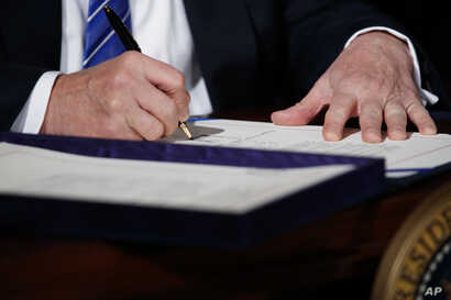 """President Donald Trump signs the """"Department of Veterans Affairs Accountability and Whistleblower Protection Act of 2017"""" in the East Room of the White House, June 23, 2017, in Washington."""
