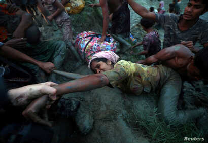 Photographers help a Rohingya refugee come out of Nad River as they cross the Myanmar-Bangladesh border in Palong Khali, near Cox's Bazar, Bangladesh, Nov. 1, 2017.