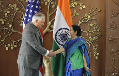 Indian Foreign Minister Sushma Swaraj, right, shakes hand with U.S. Secretary of State Rex Tillerson in New Delhi, India, Oct. 25, 2017.