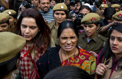 The mother (center) of the victim of the fatal 2012 gang rape that shook India arrives to lend her support at a protest in New Delhi, India, Dec. 21, 2015.