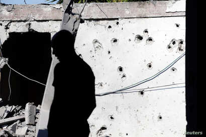 A man is silhouetted as he stands near a house damaged by a rocket fired from the Gaza Strip, in the Israeli city of Ashkelon, Nov. 13, 2018.