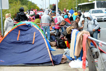 Migrants wait on a bridge for their registration and transport by German police to a refugee shelter, Sept. 24, 2015 in Salzburg, Austria at the border to Germany.