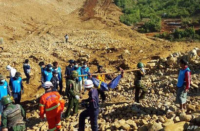 Soldiers carry the bodies of miners killed by a landslide in a jade mining area in Hpakhant, in Myanmar's Kachin state. Nov. 22, 2015.