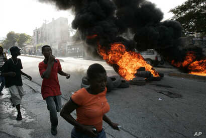FILE - Local residents run past burning tires outside the Delmas police station in Port-au-Prince, Dec 20, 2006. Riots erupted after residents surrounded the police station throwing stones and bottles demanding that the police hand over two suspected...