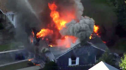In this image take from video provided by WCVB in Boston, flames consume a home in Lawrence, Mass, a suburb of Boston,  Sept. 13, 2018.