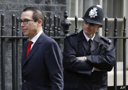 US Secretary of the Treasury Steven Mnuchin walks past a police officer at Downing Street to meet Britain's Chancellor Philip Hammond in London, Thursday, March 16, 2017.