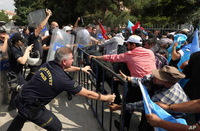 Riot police use pepper spray to push back a group of Uighur protesters who try to break through a barricade outside the Chinese Embassy in Ankara, Turkey, June 9. 2015.