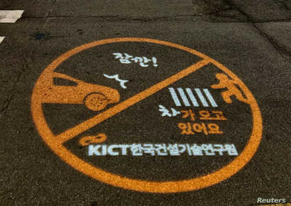 A warning sign is projected next to a zebra crossing in Ilsan, South Korea, March 12, 2019.