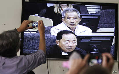 Journalists take photographs at a television screen showing the trial of Kaing Guek Eav alias Duch, former chief of the S-21 prison, at the Extraordinary Chambers in the Courts of Cambodia (ECCC) on the outskirts of Phnom Penh, February 3, 2012.