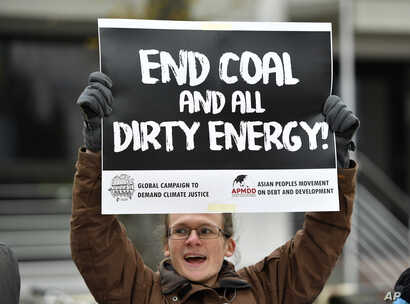 A protestor holds a sign demanding to end coal burning during the 23rd Conference of the Parties (COP) climate talks in Bonn, Germany, Nov. 15, 2017.