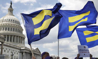"""FILE - In this July 26, 2017, photo, people with the Human Rights Campaign hold up """"equality flags"""" during an event on Capitol Hill in Washington, in support of transgender members of the military."""
