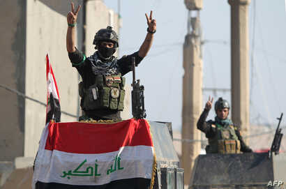 "Members of Iraq's elite counter-terrorism service flash the ""V"" for victory sign, Dec. 29, 2015 in the city of Ramadi, the capital of Iraq's Anbar province, about 110 kilometers west of Baghdad, after Iraqi forces recaptured it from the Islamic State..."
