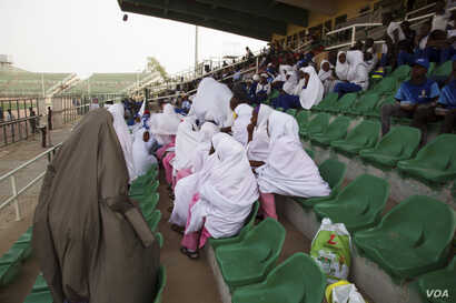Female rugby players, who wear hijab on top of their uniforms, in Kano State, Nigeria, a predominantly Muslim state, wait their turn to play at the tournament.(Photo by Chika Oduah/VOA)