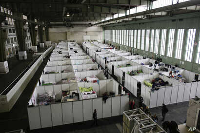 FILE - Cabins are set up inside Hanger 4 of the former airport Tempelhof to be used as a temporary emergency shelter for migrants, refugees and asylum seekers in Berlin on Dec. 9, 2015. Across Europe, gay, lesbian and transgender migrants say they su...