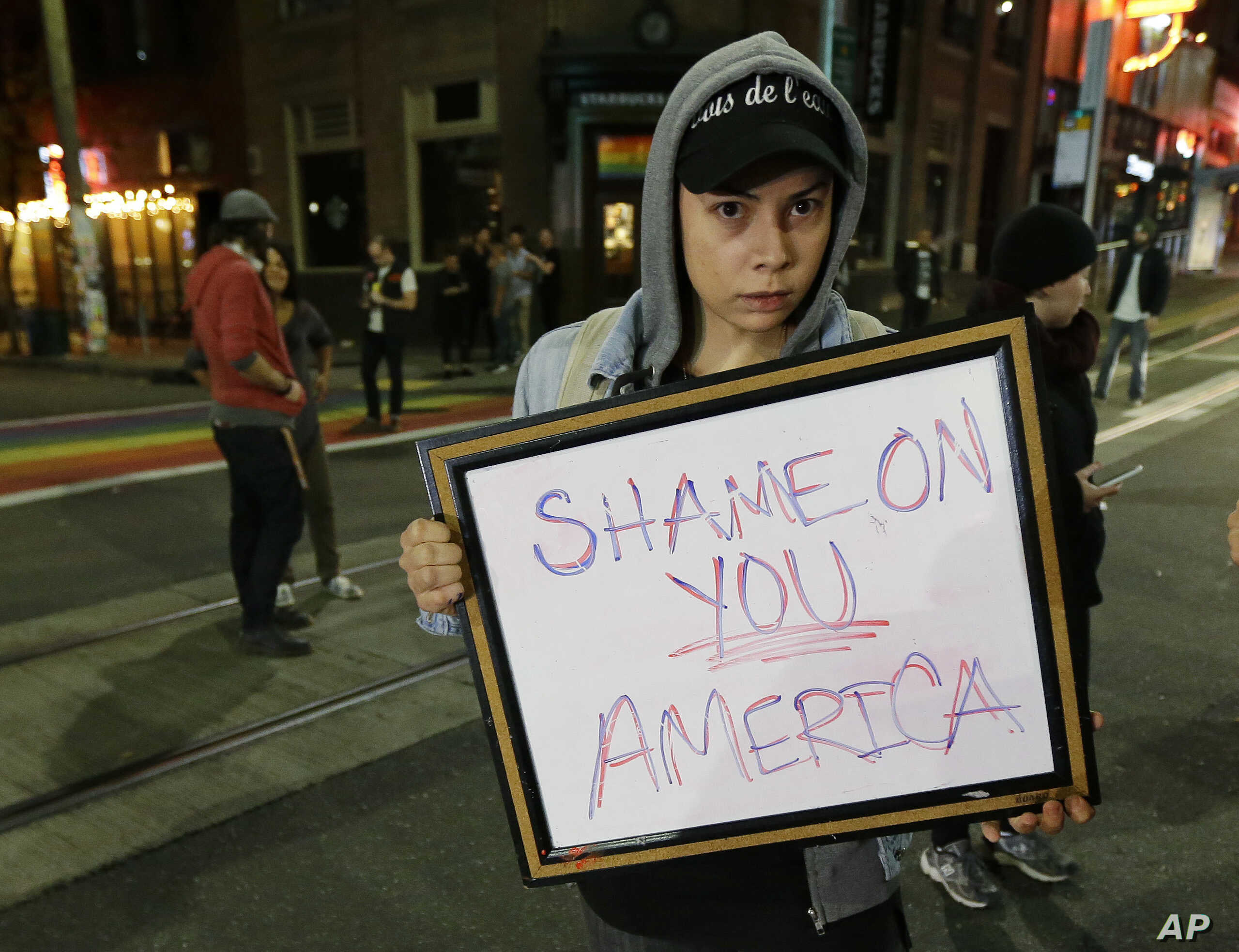 """Felomina Cervantes, of Seattle, holds a sign that reads """"Shame on You America"""" as she takes part in a protest against President-elect Donald Trump, Nov. 9, 2016, in Seattle's Capitol Hill neighborhood."""
