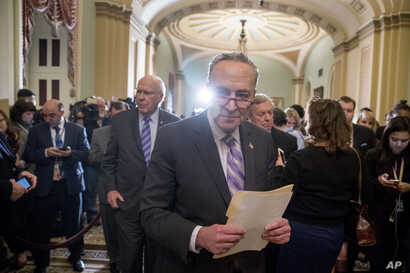 Senate Minority Leader Sen. Chuck Schumer of N.Y., center, and Sen. Patrick Leahy, D-Vt., center left, leave a new conference following a Senate policy luncheon after House and Senate negotiators worked out a border security compromise hoping to avoi...