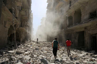 Men inspect the damage after an airstrike on the rebel held al-Qaterji neighbourhood of Aleppo, Syria, Sept. 25, 2016.