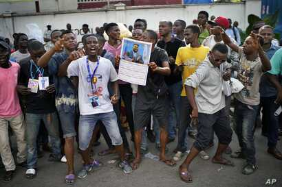 Congolese supporters of opposition Presidential candidate Felix Tshisekedi stand outside the UDPS party headquarters in Kinshasa, Congo, Jan. 7, 2019. The Congolese Independent Electoral Commission (CENI) has not given a date for the publication of p...