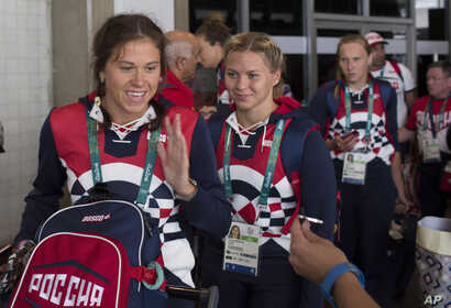 Members of the Russian Olympic delegation line up to board a bus after arriving at the Rio de Janeiro International Airport July 29, 2016, to compete at the 2016 Summer Olympics in Rio de Janeiro, Brazil.
