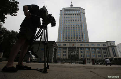 A television cameraman films the exterior of Jinan Municipality People's Intermediate Courthouse buildling, where the trial for disgraced Chinese politician Bo Xilai is likely to be held in Jinan, Shandong province, July 25, 2013. China has charged d...