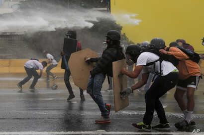 Anti-government protesters take cover from a water canon fired by security forces blocking a student march from reaching the Education Ministry in Caracas, Venezuela, May 8, 2017.