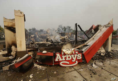 Smoke rises from an Arby's Restaurant that was destroyed by a wildfire in Santa Rosa, Calif., Monday, Oct. 9, 2017.