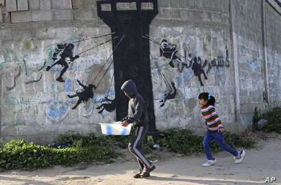 FILE - Palestinian children walk next to a mural of children using an Israeli army watch tower as a carnival ride, presumably painted by British street graffiti artist Banksy, on the main road in Beit Lahiya, in the northern Gaza Strip, Friday, Feb. ...