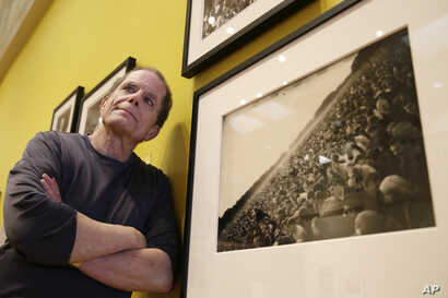 "In this Wednesday, May 10, 2017 photo, curator Dennis McNally stands by a photograph of the ""Human Be-In"" at the exhibit ""On the Road to the Summer of Love"" in the California Historical Society in San Francisco. McNally, who curated the exhibit, unco..."