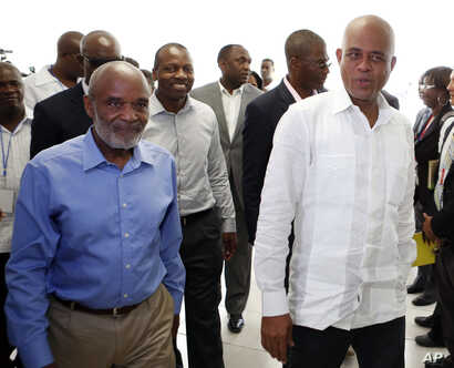 FILE - Haitian President Michel Martelly, right, walks with former Haitian President Rene Preval towards an investors luncheon before the grand opening cermony of the new Caracol Industrial Park in Caracol, Haiti.