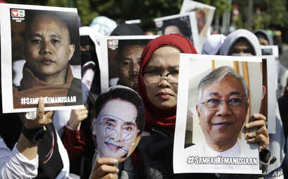 """Muslim women hold posters of Wirathu, the leader of Myanmar's nationalist Buddhist monks, Myanmar's State Counsellor Aung San Suu Kyi, and President Htin Kyaw, with writings that read """"The waste of humanity"""" during a rally against persecution of Rohi..."""