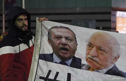 FILE - A demonstrator hold pictures of Turkey's Prime Minister Tayyip Erdogan and Turkish cleric Fethullah Gulen (R), during a protest against Turkey's ruling AK Party (AKP), demanding the resignation of Erdogan, in Istanbul Dec. 30, 2013.