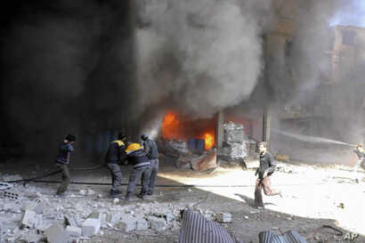 In this photo released on Feb. 20, 2018 provided by the Syrian Civil Defense group known as the White Helmets, shows members of the Syrian Civil Defense extinguishing a store during airstrikes and shelling by Syrian government forces, in Ghouta, a su...