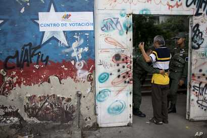 A National Guard soldier frisks a man before allowing him inside a polling station during regional elections in Caracas, Venezuela, Oct. 15, 2017.