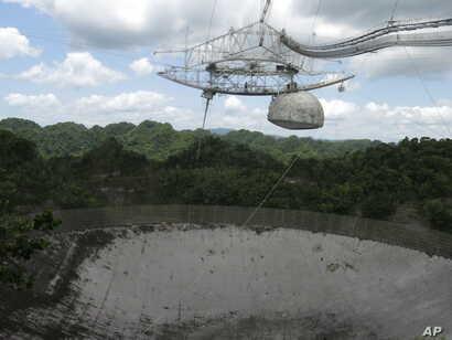 FILE - The world's largest single-dish radio telescope at the Arecibo Observatory in Arecibo, Puerto Rico, photographed July 13, 2016. Dwindling funds from the U.S. government and construction of bigger, more powerful telescopes are threatening this ...