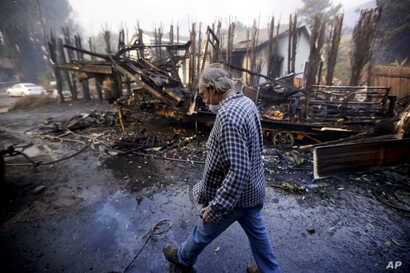 Homeowner Alan Barnard walks past the remains of his RV from a wildfire in the Lake View Terrace area of Los Angeles, Dec. 5, 2017.