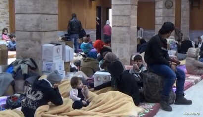 A still image taken from a video,  said to be shot Jan.  4, 2017, shows civilians, who were evacuated from Wadi Barada, sitting inside a shelter in the Damascus suburb of Rawda, Syria.