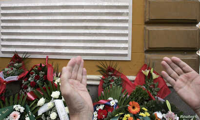 FILE - A Bosnian man prays in front of a memorial plague during the 13th anniversary of the shelling from neighboring hills by the Bosnian Serb forces in the capital Sarajevo, Aug. 28, 2008.