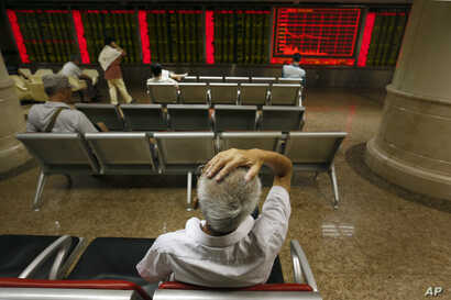 Chinese investors monitor stock prices at a brokerage house in Beijing, Aug. 24, 2015.