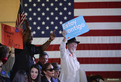 """Supporters of Democratic U.S. presidential candidate Hillary Clinton hold up signs as they wait for her to speak at a """"Latinos for Hillary"""" rally in San Antonio, Texas, Oct. 15, 2015."""