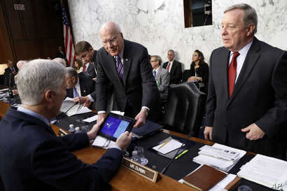 Sen. Richard Durbin, D-Ill., right, and Sen. Patrick Leahy, D-Vt., center, speak with Supreme Court Justice nominee Neil Gorsuch, left, on Capitol Hill in Washington, March 21, 2017, before the start of his confirmation hearing before the Senate Judi...